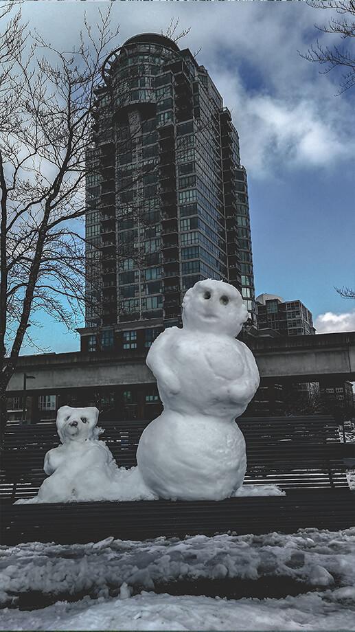 Schneemänner auf Parkbank vor Hochhaus in Vancouver
