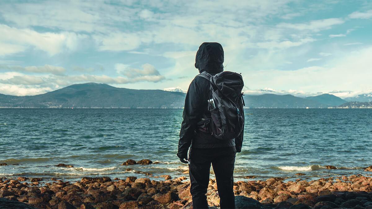 Person an Steinstrand Pazifik mit Bergen am Horizont
