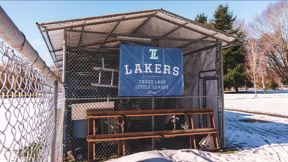 Unterstand aus Maschendraht mit Banner der Sportmannschaft Lakers