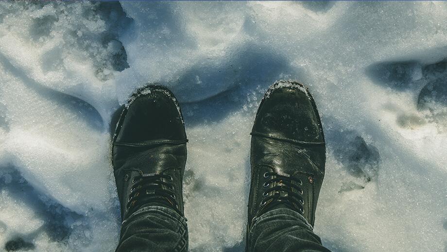 Blick von oben auf schwarze Stiefel im Schnee